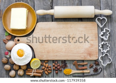 Baking cookies with spices and empty cutting board abstract background - stock photo