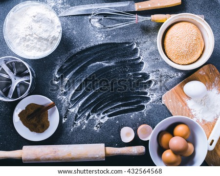 Baking dark background with blank cook book, eggshell, bread, flour, rolling pin. Ingredients for the baking. - stock photo