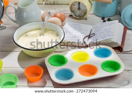 Baking fresh muffins with blueberries - stock photo
