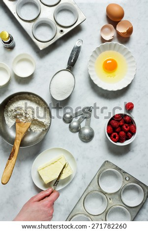 Baking: Hand Cuts Into Butter With Ingredients to Make Raspberry Muffins Scattered Around Counter - stock photo