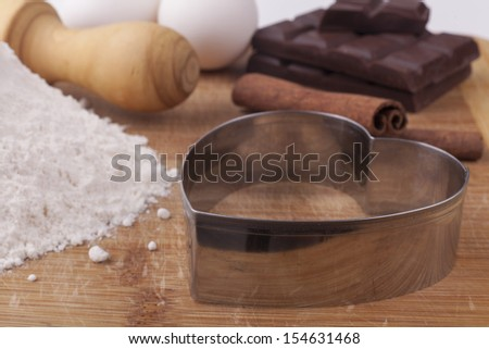 Baking ingredients an tools on brown wood cutting board focus on the metal heart shape
