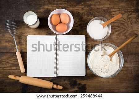 baking ingredients and blank cookbook on dark wooden table - stock photo