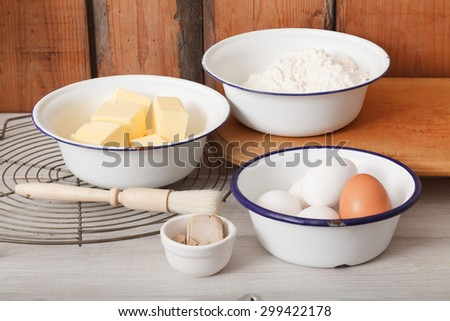 Baking ingredients butter, eggs, yeast and flour in bowls