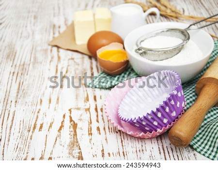 Baking ingredients - eggs, flour, and butter on a wooden background