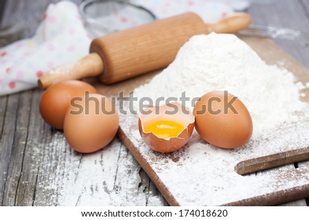 Baking ingredients - flour, eggs and rolling pin on a table - stock photo