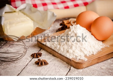 Baking ingredients - flour, eggs, butter and rolling pin on a table