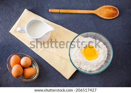 Baking ingredients - flour, milk and eggs with a wooden spoon and napkin on a slate background
