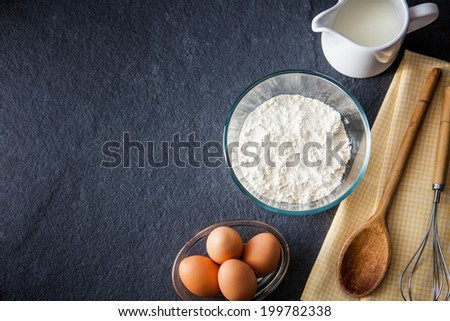 Baking ingredients - flour, milk, eggs with a whisk, wooden spoon and napkin on a slate background