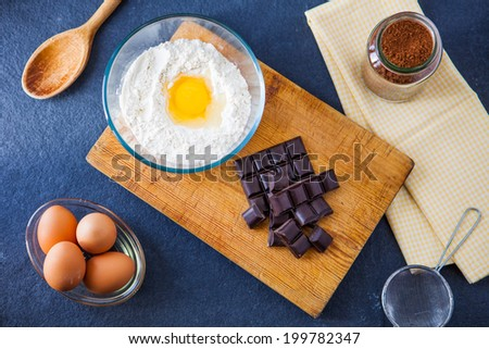 Baking ingredients for a chocolate cake - flour, eggs, chocolate, cocoa powder with a wooden spoon, sieve and napkin on a slate background