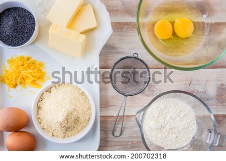 Baking ingredients for a lemon cake - flour, eggs, butter, ground almonds, lemon zest and poppy seeds - stock photo