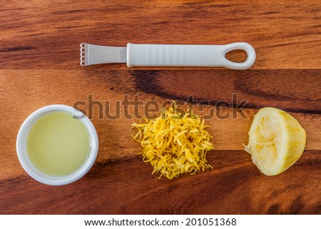 Baking ingredients for a lemon cake - lemon rind, squeezed lemon, lemon juice and lemon zester on a wooden background - stock photo