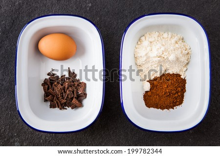 Baking ingredients for chocolate cake - flour, egg, chipped chocolate and cocoa powder on a slate background