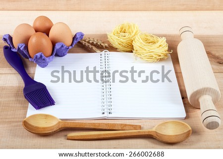 Baking ingredients for cooking and notebook for recipes on a wooden board. - stock photo