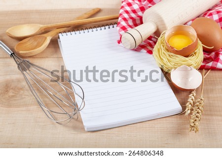 Baking ingredients for cooking and notebook for recipes on a wooden table. - stock photo