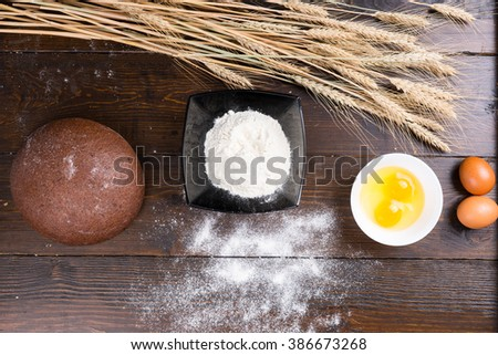 Baking ingredients for making fresh bread displayed on a wooden table with eggs, flour, ears of wheat and a fresh round bread loaf, overhead view - stock photo