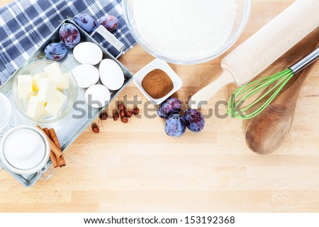baking ingredients from top for a plum cake on wooden background - stock photo
