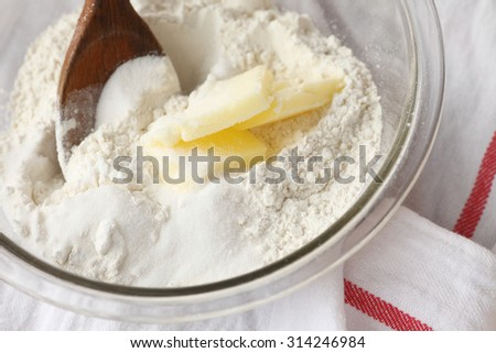 Baking ingredients in a mixing bowl with a wooden spoon on dishcloth - stock photo