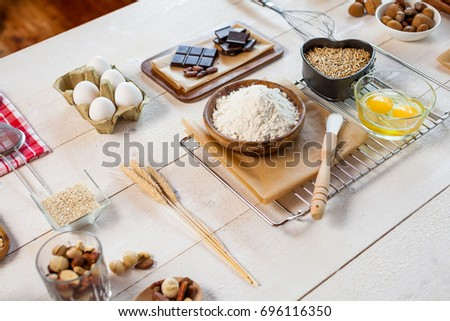 Baking ingredients in rural kitchen - dough recipe ingredients (eggs, flour, milk, butter, sugar) and rolling pin on wooden white table.