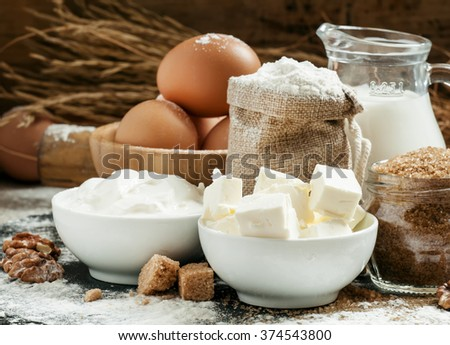 Baking ingredients: milk, butter, flour, sugar, eggs and rolling pin on a floured table in a rustic style, selective focus