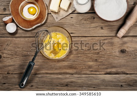 Baking ingredients (milk, eggs, flour, butter) in the bakery on a rustic table. Top view. Copy space - stock photo
