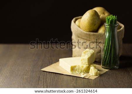 Baking potatoes in a sack with chives and cheddar cheese - stock photo