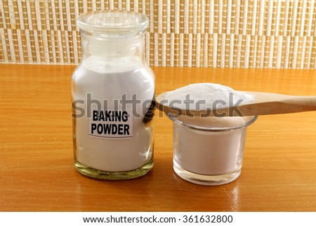 baking powder in glass bottle and wooden spoon - stock photo