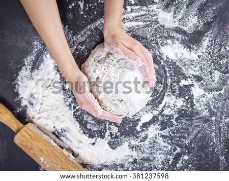 Baking preparing background. Female hands knead dough on the worktop. - stock photo