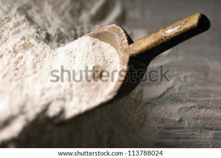 Baking scoop defocus in a heap of flour - stock photo