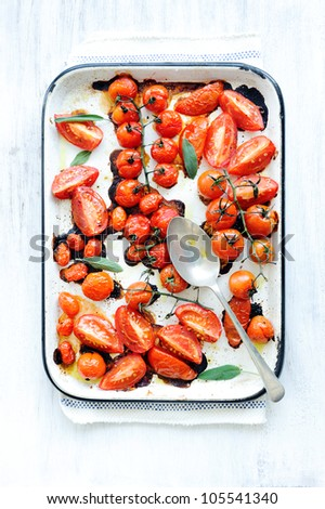 Baking tray filled with delicious juicy oven roasted organic tomatoes with fresh sage leaf herb and olive oil - stock photo