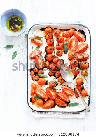 Baking tray filled with delicious juicy oven roasted tomatoes with fresh sage leaf herb and olive oil  - stock photo