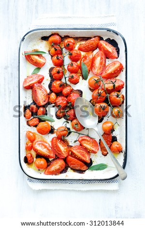 Baking tray filled with delicious juicy oven roasted tomatoes with fresh sage leaf herb and olive oil