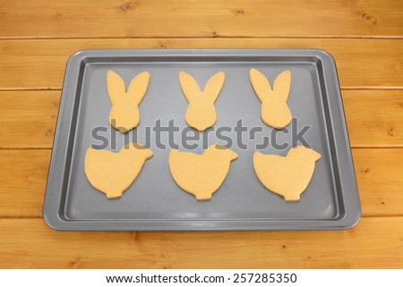 Baking tray with six Easter cookies - bunnies and chicks - on a wooden table - stock photo