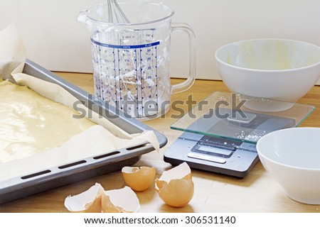 baking utensils, baking tray with dough, plastic jug, kitchen scales, bowls and eggshells on a wooden worktop - stock photo