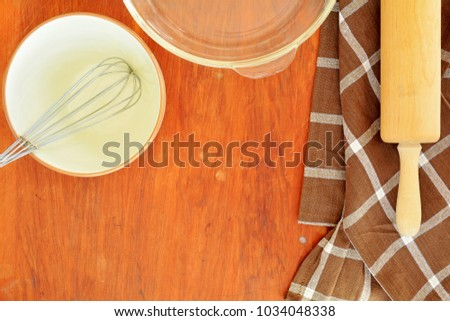 Baking utensils on old wooden background in flat lay with room for text