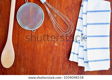 Baking utensils on vintage wooden board in flat lay format with room for text