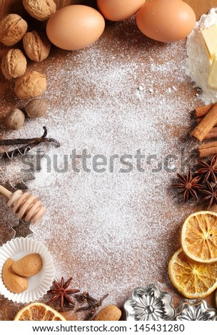Baking utensils, spices and food ingredients on wooden background with copy space. - stock photo