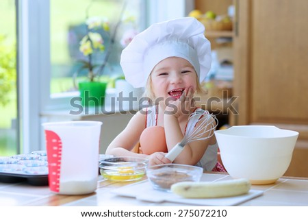 Baking with children: little happy kid, adorable toddler girl in white chef hat helping mother to prepare delicious muffins in the kitchen. Bowl, flour, butter and banana on the table. - stock photo