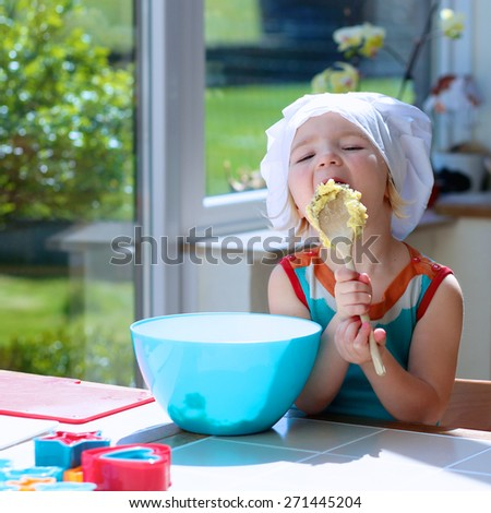 Baking with children: little happy kid, adorable toddler girl in white chef hat mixing and tasting dough ingredients in the bowl helping mother to prepare delicious pastry in the kitchen