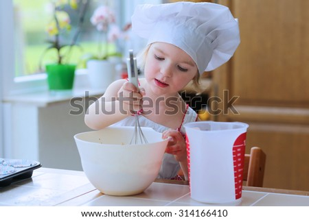 Baking with children: little happy kid, adorable toddler girl in white chef hat mixing dough ingredients in the bowl helping mother to prepare delicious pastry in the kitchen - stock photo