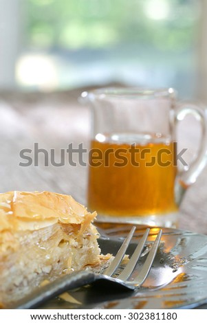 Baklava, delicious pastry dessert made with phyllo dough, nuts, butter and sugar served on a plate with a jar of honey - stock photo