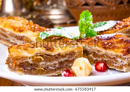 Baklava with honey and nuts on white plate