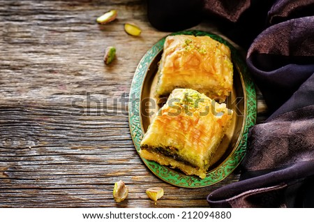 baklava with pistachio. turkish traditional delight on a dark wood background. toning - stock photo