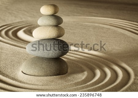 balance and harmony in zen meditation garden relaxation and simplicity for concentration. Sand and stone form nice lines and pattern - stock photo