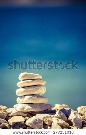 Balance and wellness retro spa concept, inspiration, zen-like and well being tranquil composition. Close-up of white pebbles stack over blue sea - stock photo