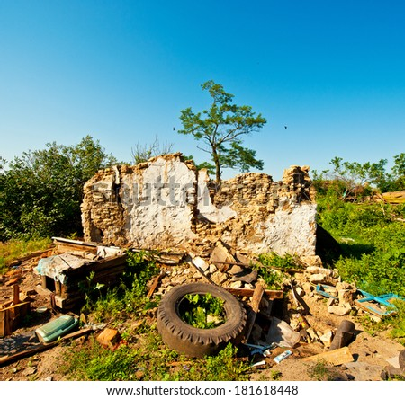 balance of the wall of the old destroyed houses and debris in the countryside, spring day