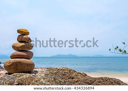 balance rock or balance zen stone on relaxing beach on day noon light abstract background for zen spa or alternative therapy on vacation beach.  - stock photo