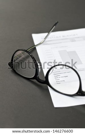 Balance sheet and eye glasses on the table - stock photo