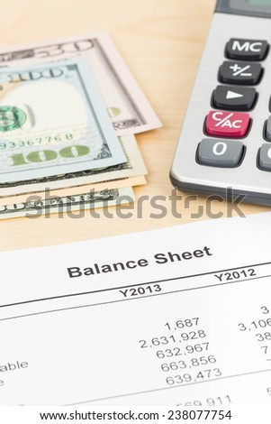 Balance sheet financial report with pen, banknote, and calculator - stock photo