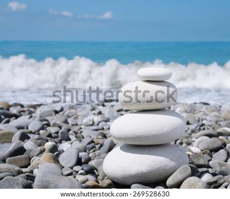 balance white stones zen-like on a pebble beach - stock photo