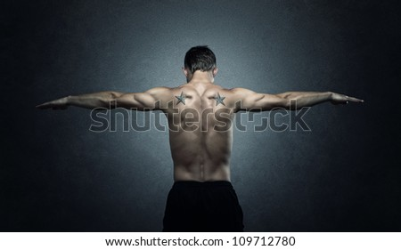 Balance, young adult stretching out arms over dark background - stock photo